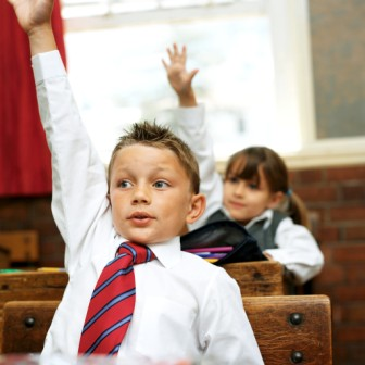 Young Boy at School Raising His Hand to Answer in Class --- Image by © Royalty-Free/Corbis